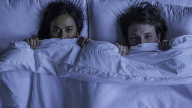 Zwei junge Menschen fürchten sich im Bett