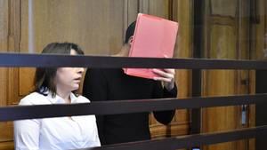 Swetoslaw S., ein schlanker junger Mann in schwarzem Pullover, versteckt im Gerichtssaal sein Gesicht hinter einer roten Mappe
