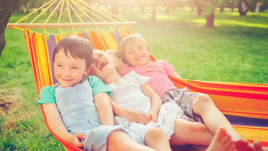 Drei Kinder liegen in einer Hängematte und lachen