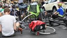 Auf einer Straße in Berlin-Neukölln sitzen Radfahrer neben ihren auf den Asphalt gelegten Fahrrädern