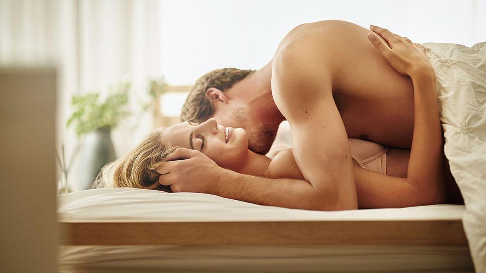 Ein Mann küsst den Hals einer Frau auf einem Bett