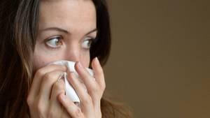 Eine Frau weint nach einer Trennung in ein Taschentuch (Symbolbild)