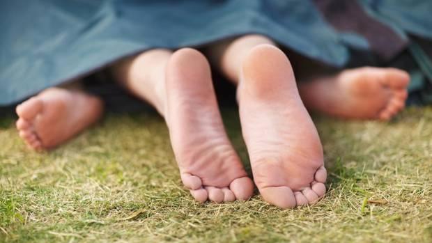 Füße gucken unter einer Decke auf einer Rasenfläche hervor