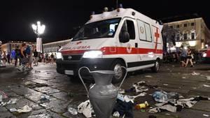 Ein Krankenwagen fährt in Turin nach der Massenpanik an einer Nachbildung des Champions-League-Pokals vorbei