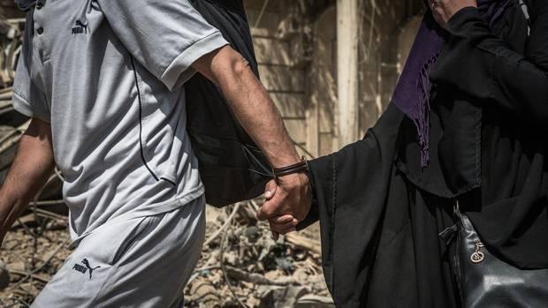 Zwei Zivilisten flüchten aus dem schwer umkämpften Mossul im Irak. Ein neuer UN-Bericht zählt die Flüchtlinge weltweit.