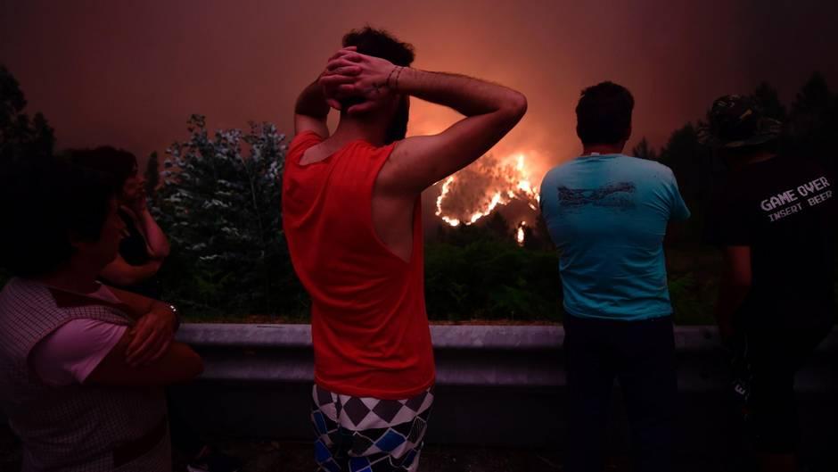 Bewohner blicken auf einen Waldbrand in der Nähe des Dorfes Mega Fundeira in Portugal