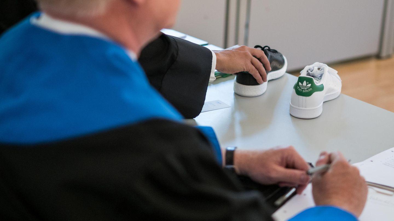"""Adidas Sportschuhe des Models """"Stan Smith"""" stehen bei der Verhandlung gegen Puma auf einem Tisch im Landegericht Braunschweig."""