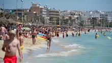 Touristen im Urlaub an einem Strand auf Mallorca