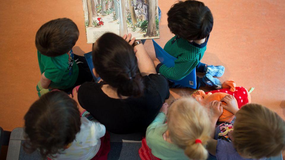 Eine Mutter liest Kindern ein Buch vor
