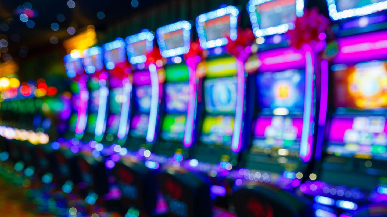 Eine Reihe von bunt beleuchteten Spielautomaten in einem Casino