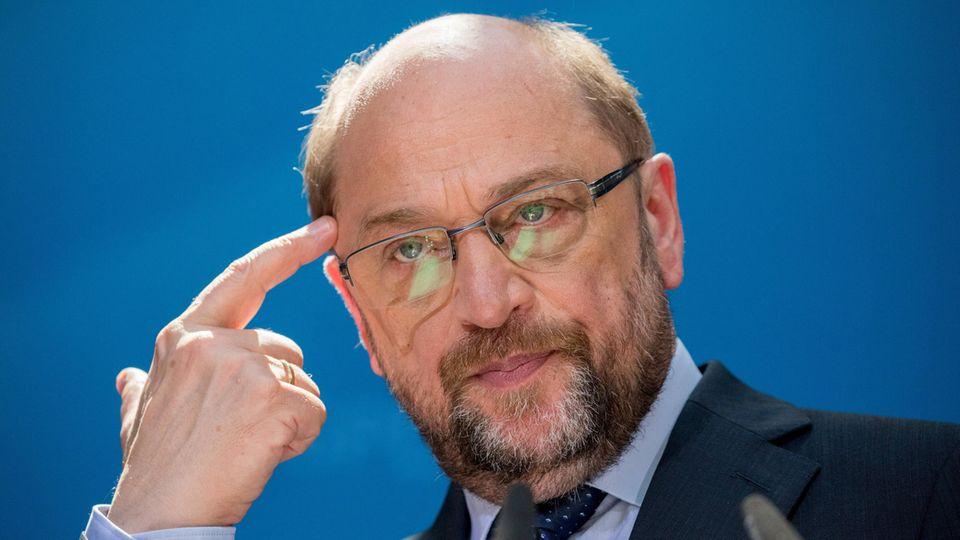 Martin Schulz tippt sich an die Stirn während er das SPD-Steuerkonzept vorstellt