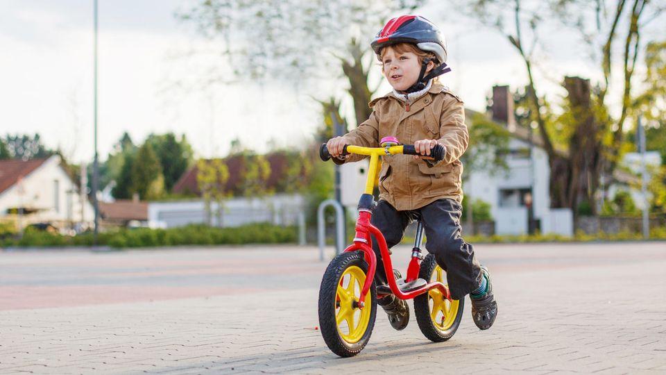 Ein Junge auf einem Laufrad (Symbolbild)