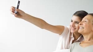 Eine Jugendliche und eine ältere Frau lachen zusammen für ein Selfie