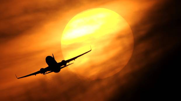 Hitzewelle in den USA - Ein Flugzeug fliegt vor der untergehenden Sonne