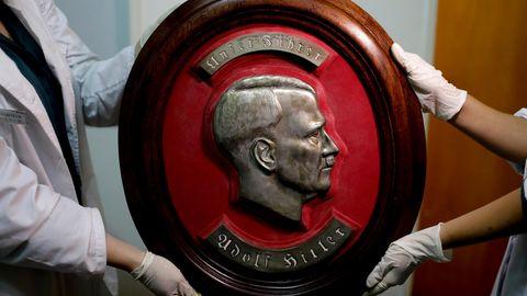Mitglieder der Bundespolizei zeigen im Interpol-Hauptquartier in Buenos Aires ein gefundenes Relief von Adolf Hitler