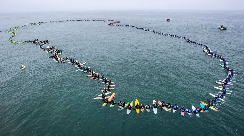 """Juni    Huntington Beach, USA: Surfer formen einen Kreis auf dem Ozean und halten sich dabei an den Händen. Das Ritual wird """"Paddle Out"""" genannt und gilt normalerweise dem Gedenken verstorbener Surfer. 511 Surfer nahmen an dem """"Paddle Out"""" teil, sie stellten einen neuen Weltrekord für die meisten Teilnehmer an dem Ritual auf."""