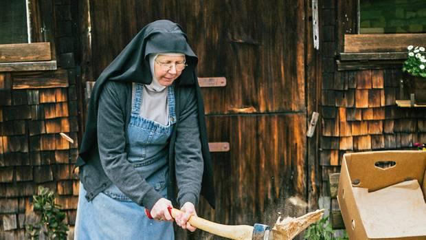Schwester Dominica im Habit beim Holzhacken. Auch mit der Motorsäge kann sie umgehen