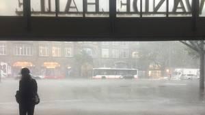 Eine Passantin steht während eines starken Gewitters in der Wandelhalle des Hauptbahnhofs in Hamburg