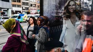 Frauen warten an einer Bushaltestelle in Istanbul (Türkei) neben einem Plakat mit US-Schauspielerin Julia Roberts