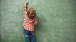 Ein kleiner Junge schreibt mit links Mathe-Aufgaben an die Tafel