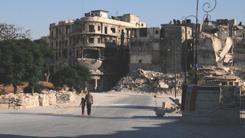 Ein Vater geht mit seiner Tochter in der Nähe der alten Zitadelle von Aleppo spazieren