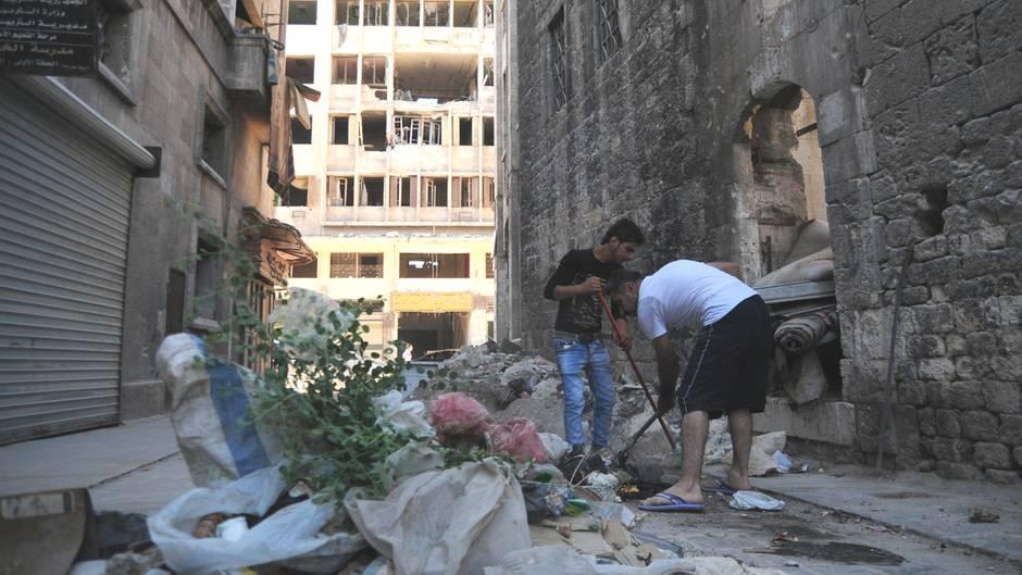Anwohner räumen im Westen Aleppos Trümmer und Schutt von der Straße