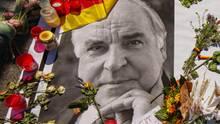 Kerzen und Blumen stehen auf einem Bild des verstorbenen Helmut Kohl