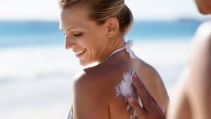 Eine Frau cremt sich mit Sonnencreme ein.