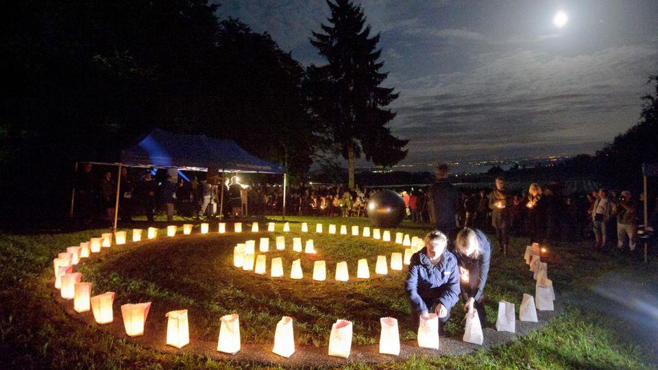 Gedenkstätte in Überlingen-Brachenreuthe im Bodenseekreis: Anlässlich des zehnten Jahrestages des Absturzes stellen Jugendliche Kerzen für die Opfer des Flugzeugabsturzes in Form einer Spirale auf.