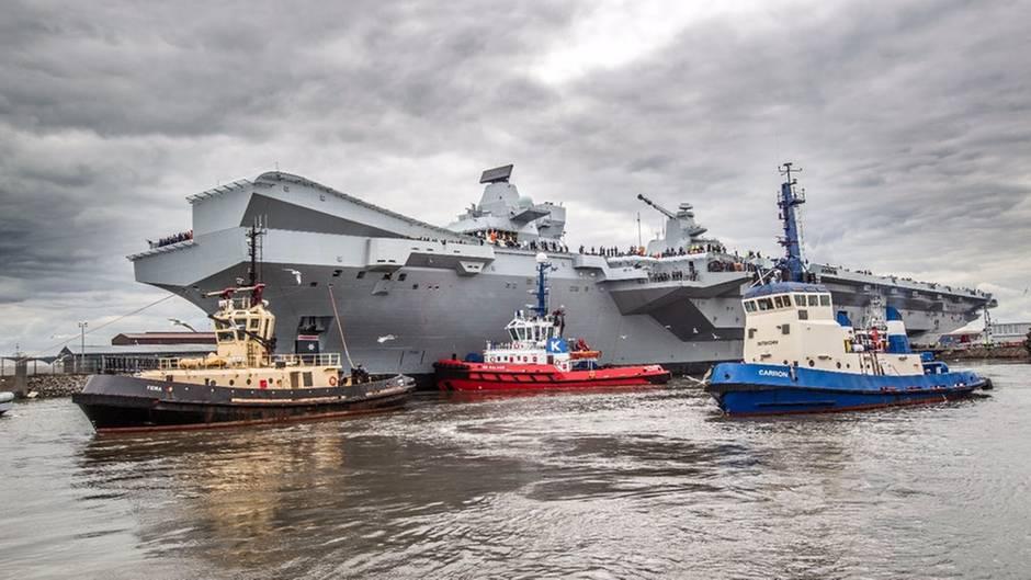"""Die Schlepper bringen die """"HMS Queen Elizabeth"""" auf ihre erste Reise."""