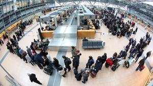 Lange Schllangen:Flugpassagiere warten am Flughafen in Hamburg auf die Abfertigung an den Check-In-Schaltern.