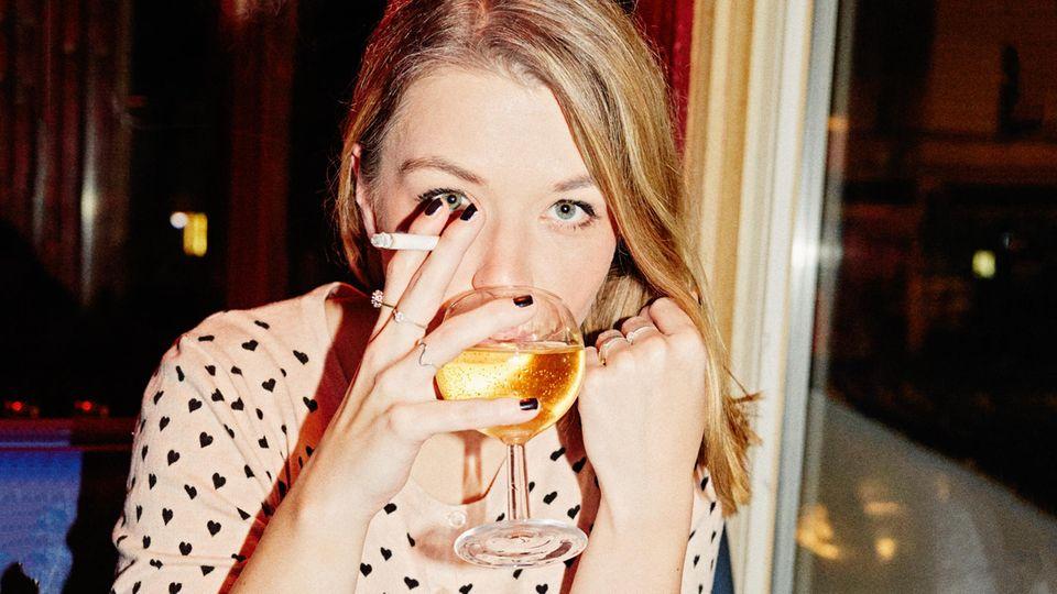 Julia Schramm mit Zigarette und einem Glas Weißwein