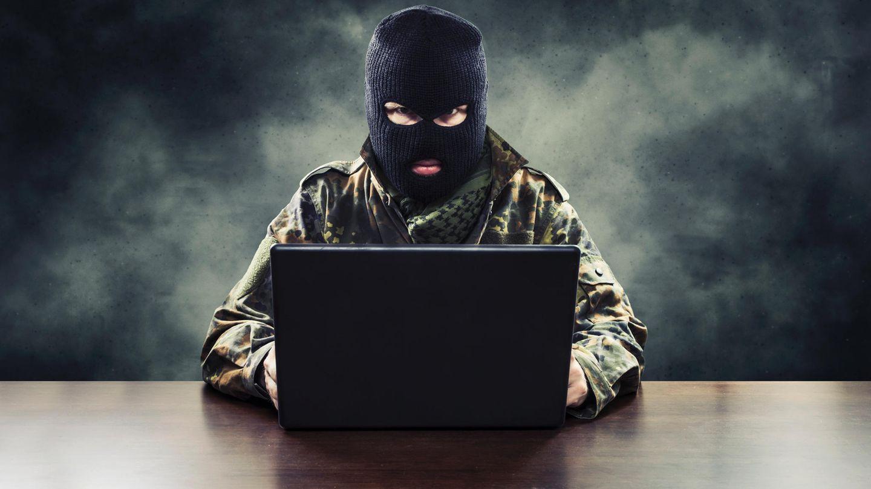 Ein Mann sitzt mit Militärkleidung und Sturmmaske vor seinem Laptop