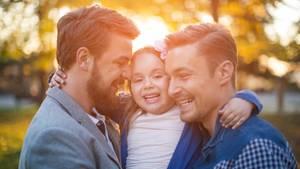 Zwei Väter, lächelnd mit ihrer Tochter auf dem Arm.