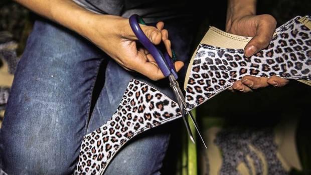 Nuri schneidet Plastik für die Schuhe zurecht. Bald will er an einer Nähmaschine arbeiten, sagt er. Das ist sein Ziel. Außerdem denkt er ans Heiraten