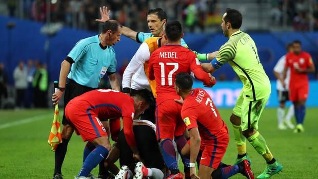 Der deutsche Nationalspieler Emre Can ist von chilenischen Spielern umringt