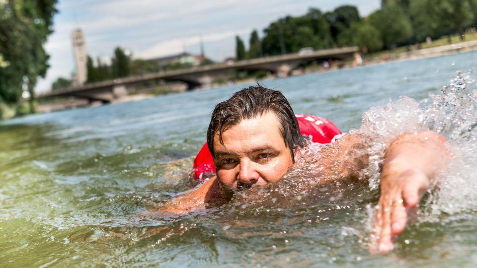 Ein Mann mit Rucksack schwimmt durch die Isar