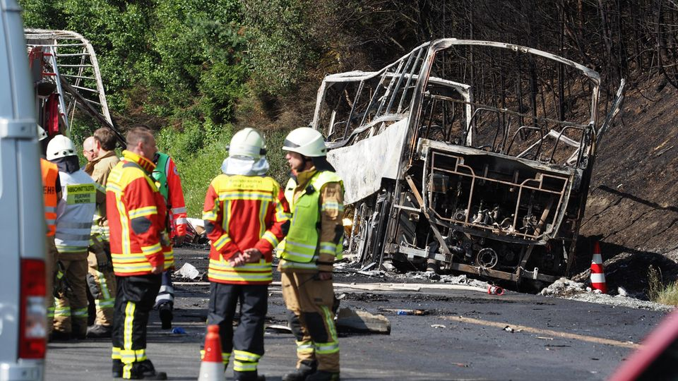 Busunglück auf der A9 in Bayern: Der ausbrannte Bus liegt am Straßenrand, davor stehen Einsatzkräfte der Feuerwehr