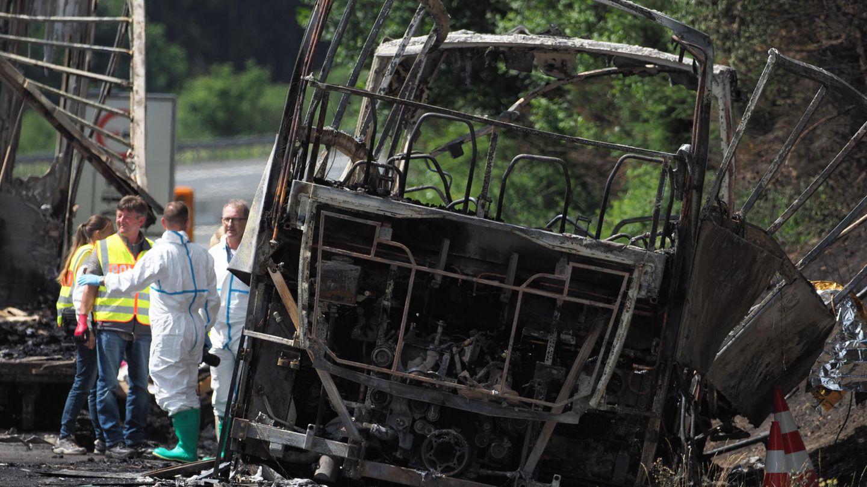 Experten der Polizei arbeiten in Münchberg (Bayern) an der Unfallstelle auf der Autobahn A9 neben dem Gerippe des Busses