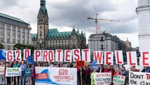 """Aktivisten der geplanten Protestaktion """"G20-Protestwelle"""" werben vor dem Hamburger Rathaus für die Akltion"""