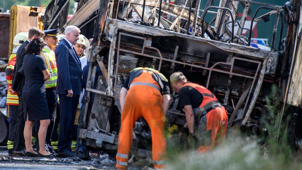 Busunglück in Bayern: Ministerpräsident Horst Seehofer steht zusammen mit Einsatzkräften an dem verunfallten Reisebus.