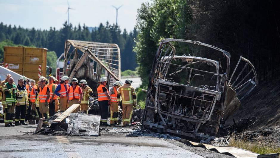 Hilfskräfte der Feuerwehr und Rettungskräfte vor dem vollkommen ausgebrannten Wrack des Reisebusses.