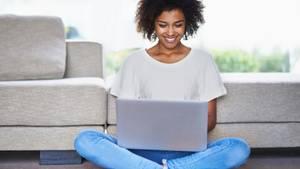 Eine Frau sitzt zuhause mit dem Laptop auf dem Boden und lächelt