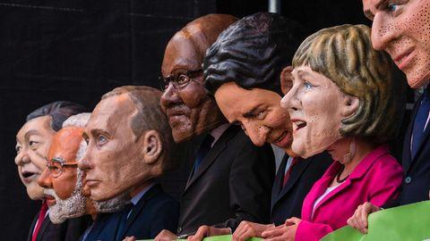 Auf einer Demo vor dem G20-Gipfel tragen Schausteller Masken der Staatschef der Teilnehmernationen