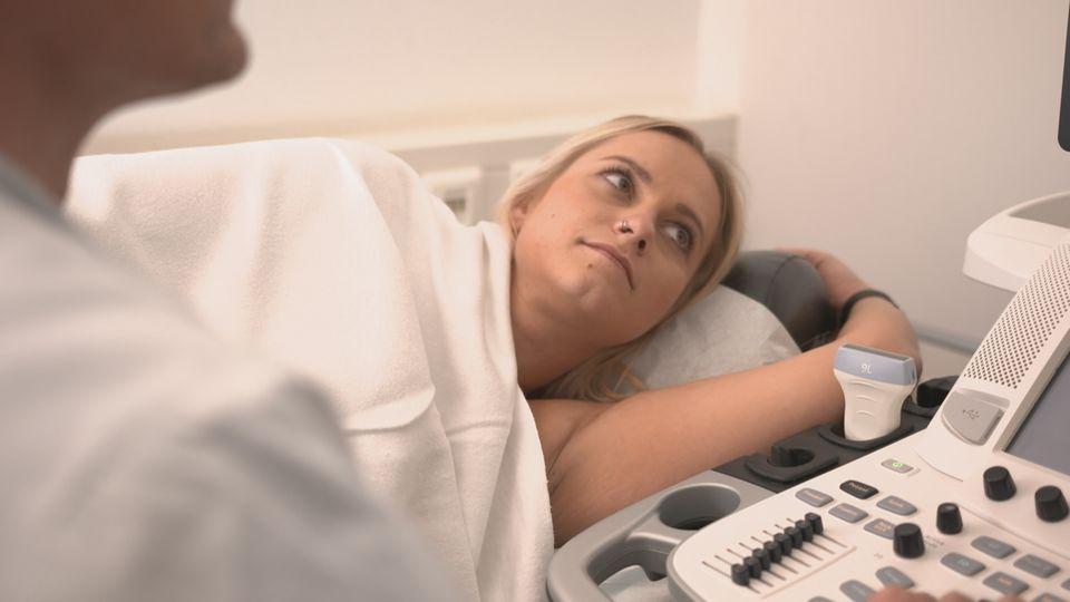Sarah während einer Untersuchung. Von der Behandlungsliege aus schaut sie auf einen Monitor, der neben ihr steht.