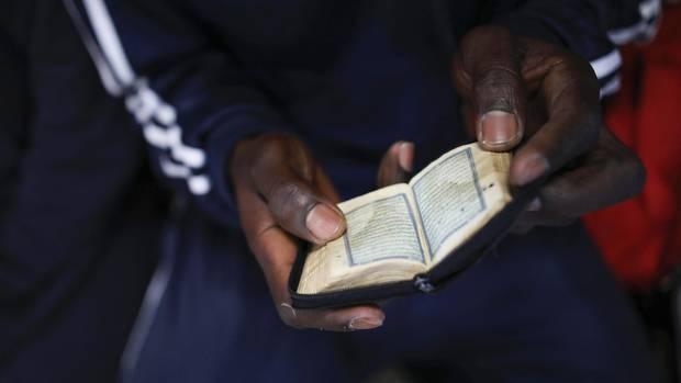 Während er auf die Ankunft in Italien wartet liest dieser Mann im Koran