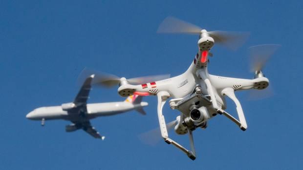 Eine private Drohne fliegt in knapp 10 Metern Flughöhe über dem Boden, während in weiter Entfernung ein Flugzeug zu sehen ist.