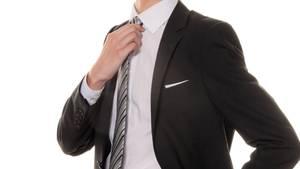 Ein Mann im Anzug rückte seine Krawatte zurecht (Symbolfoto)