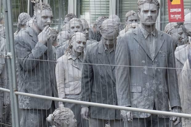 Graue Gestalten hinter einem Zaun