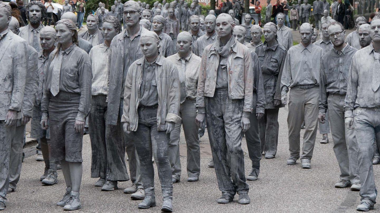 Grau gekleidete Akteure marschieren gegen G20